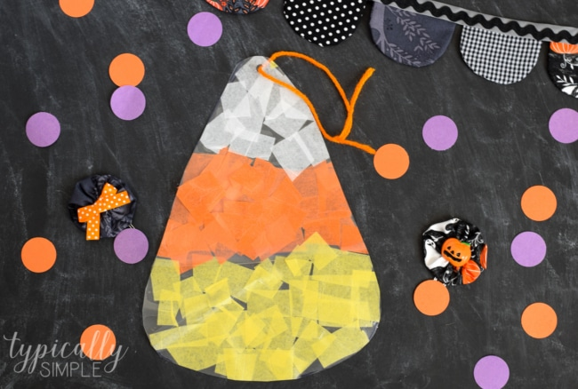 This tissue paper candy corn craft is such a fun craft to make with the kids for Halloween! Hang it in a window for a not-so-spooky sun catcher!